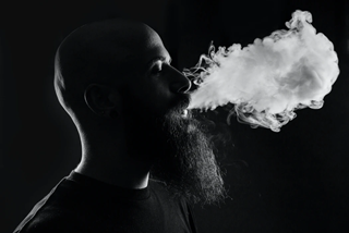 man smoking an e-liquid smoke cloud